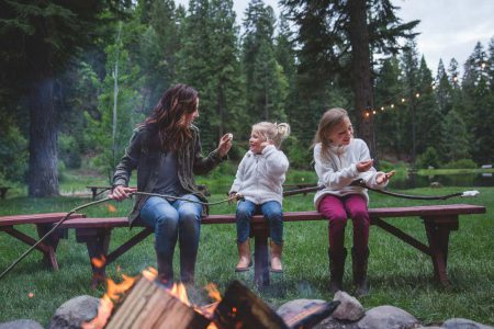 A mom and two daughters roasting marshmallows at the campfire