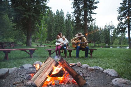 A mom and two daughters at the campfire enjoying some acoustic guitar.