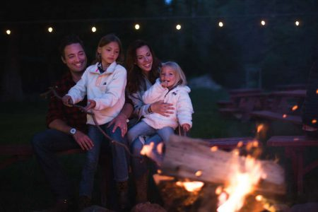 A family enjoying s'mores around the campfire at the Ranch