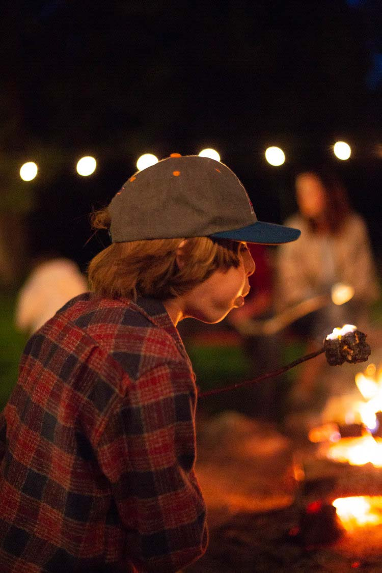 A child blowing out a marshmallow near a campfire at Greenhorn Ranch