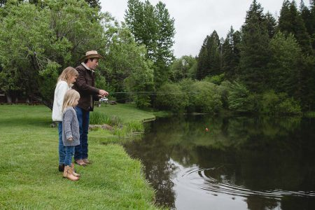 A father & two daughters fishing at the lake at the Greenhorn Ranch in Quincy, CA