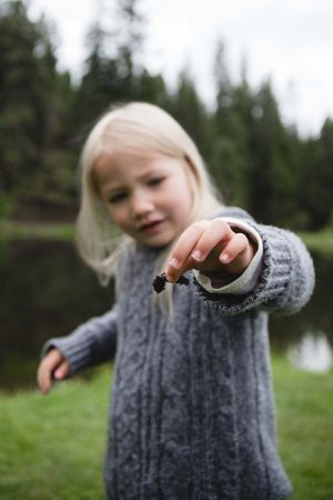 A little girl holding a worm while fishing at the lake