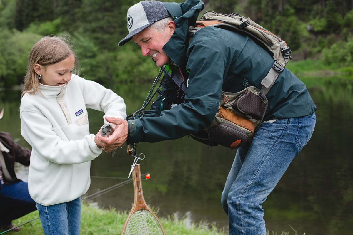 A girl holding a fish she caught fishing at the lake at the Greenhorn Ranch