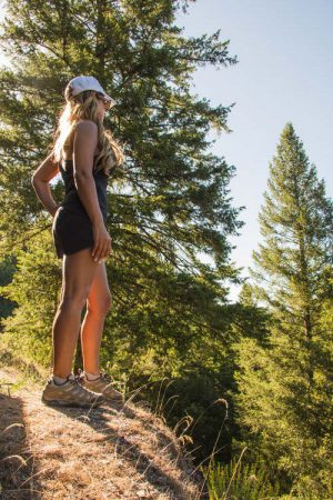 A runner stopping to enjoy the view during a trail run through the forest.