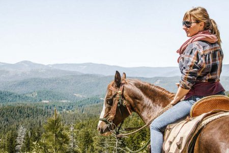 A woman on horseback overlooking the pine forest valley at Greenhorn Ranch