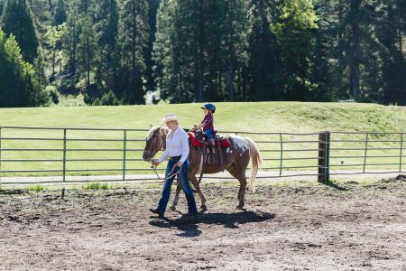 A young child on a lead-around ride in the arena at Greeenhorn Ranch