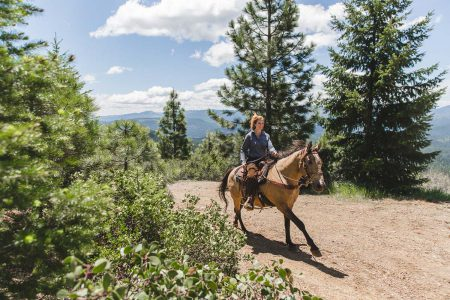 Loping on horseback through the pine forest at Greenhorn Ranch