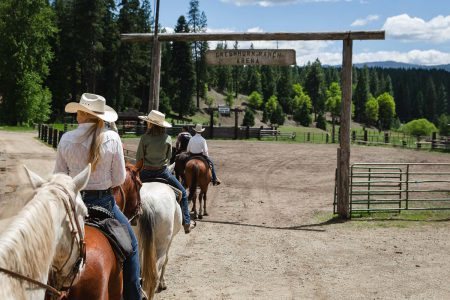 A group on horseback re-entering the arena after a trail ride at Greenhorn Ranch