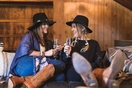 Two friends enjoying champagne at the lodge