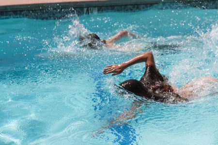 Two sisters racing in the pool on a warm summer day at Greenhorn Ranch