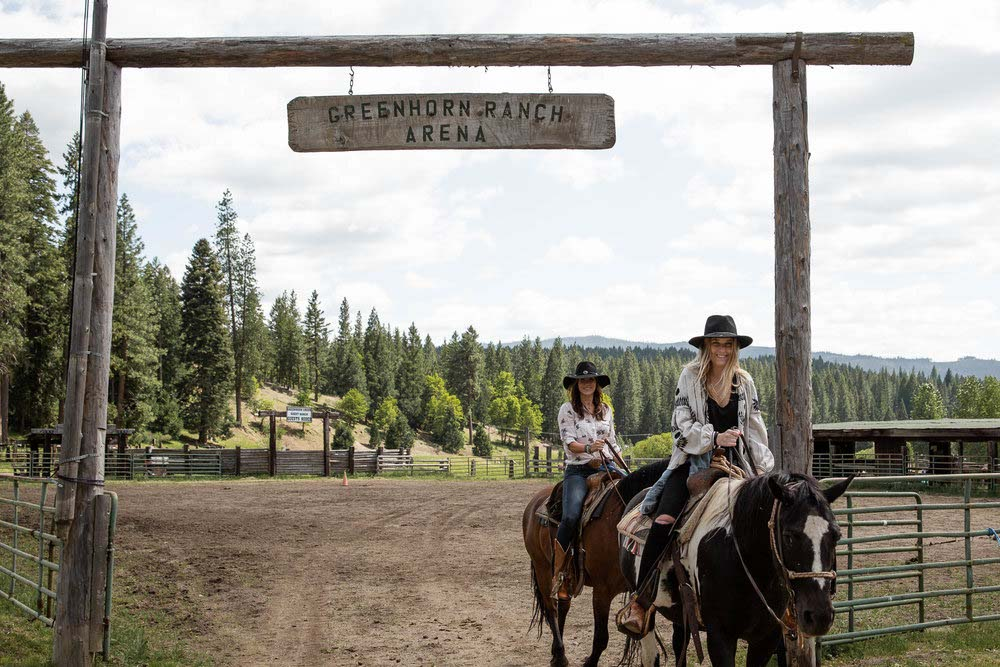 A group horseback ride leaving the Greenhorn Ranch arena and headed for the hills