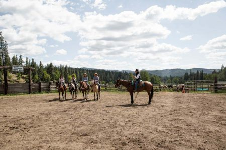 A wrangler and four horseback riders in the Greenhorn Ranch arena