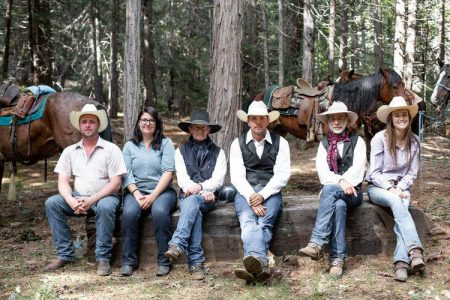 6 horseback riders sitting on a wall in the pine forest while taking a break at Greenhorn Ranch