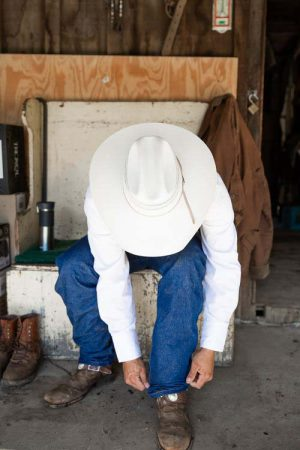 A man adjusting his denim pants over his riding boots before a horseback ride at Greenhorn Ranch