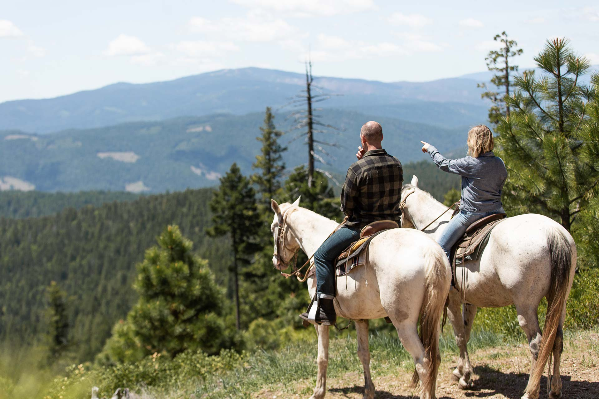 A couple on a horseback ride overlooking the mountains of California at the Greenhorn Ranch in Quincy, CA