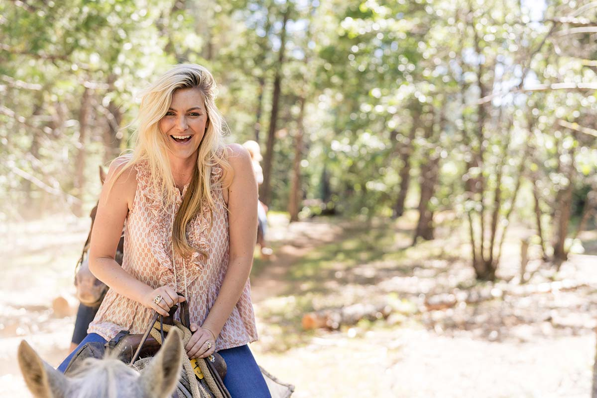 A young woman smiling while riding a horse through the woods at Greenhorn Ranch in the Sierras of California