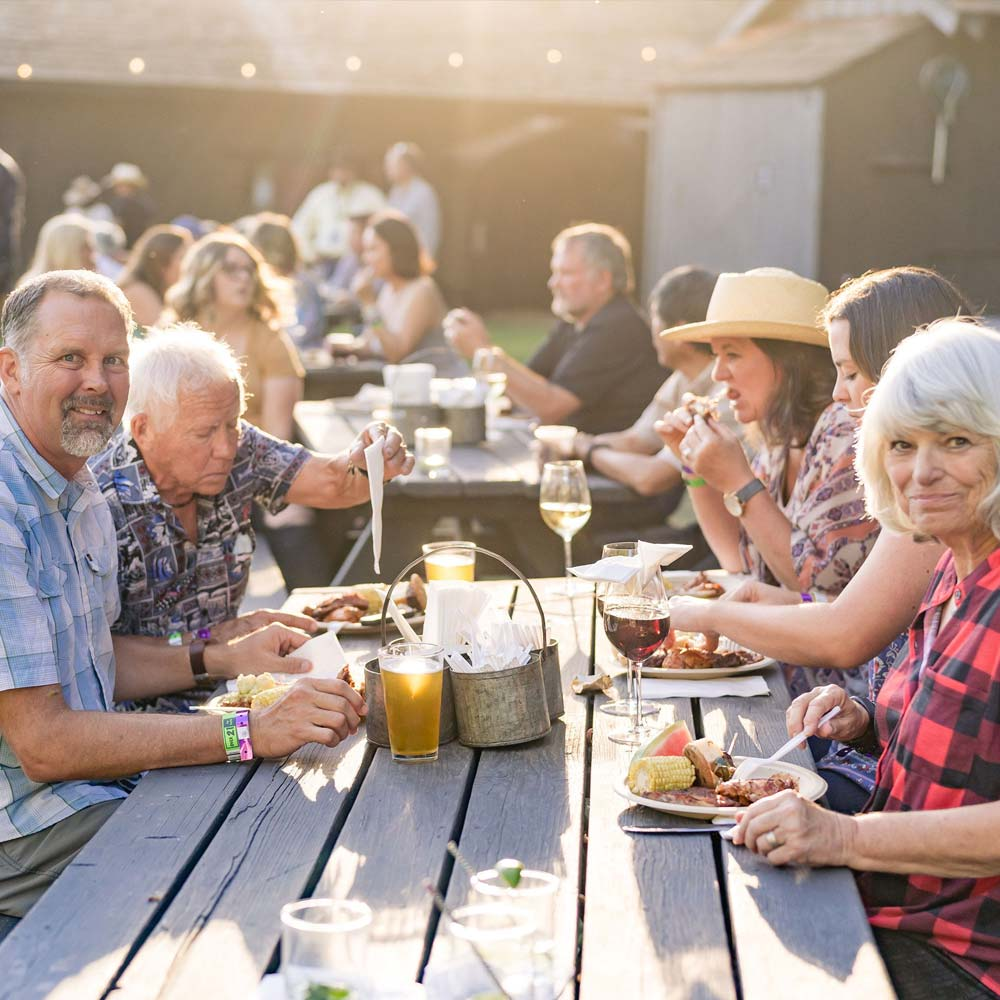 Food Activities at Greenhorn Ranch - People eating at a picnic table in the golden sunlight