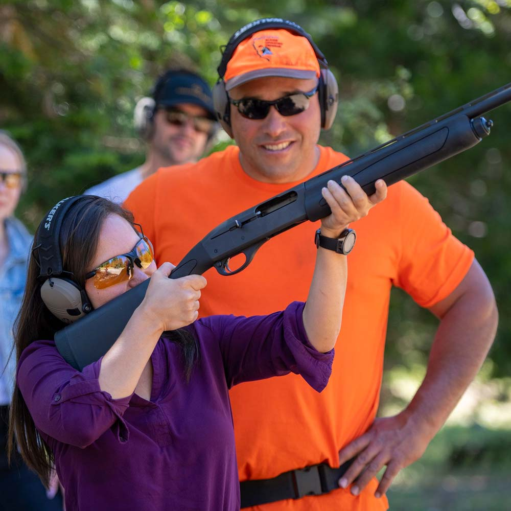 Shooting Sports at Greenhorn Ranch - a Ranch guest shooting clay pigeons while a safety instructor helps her