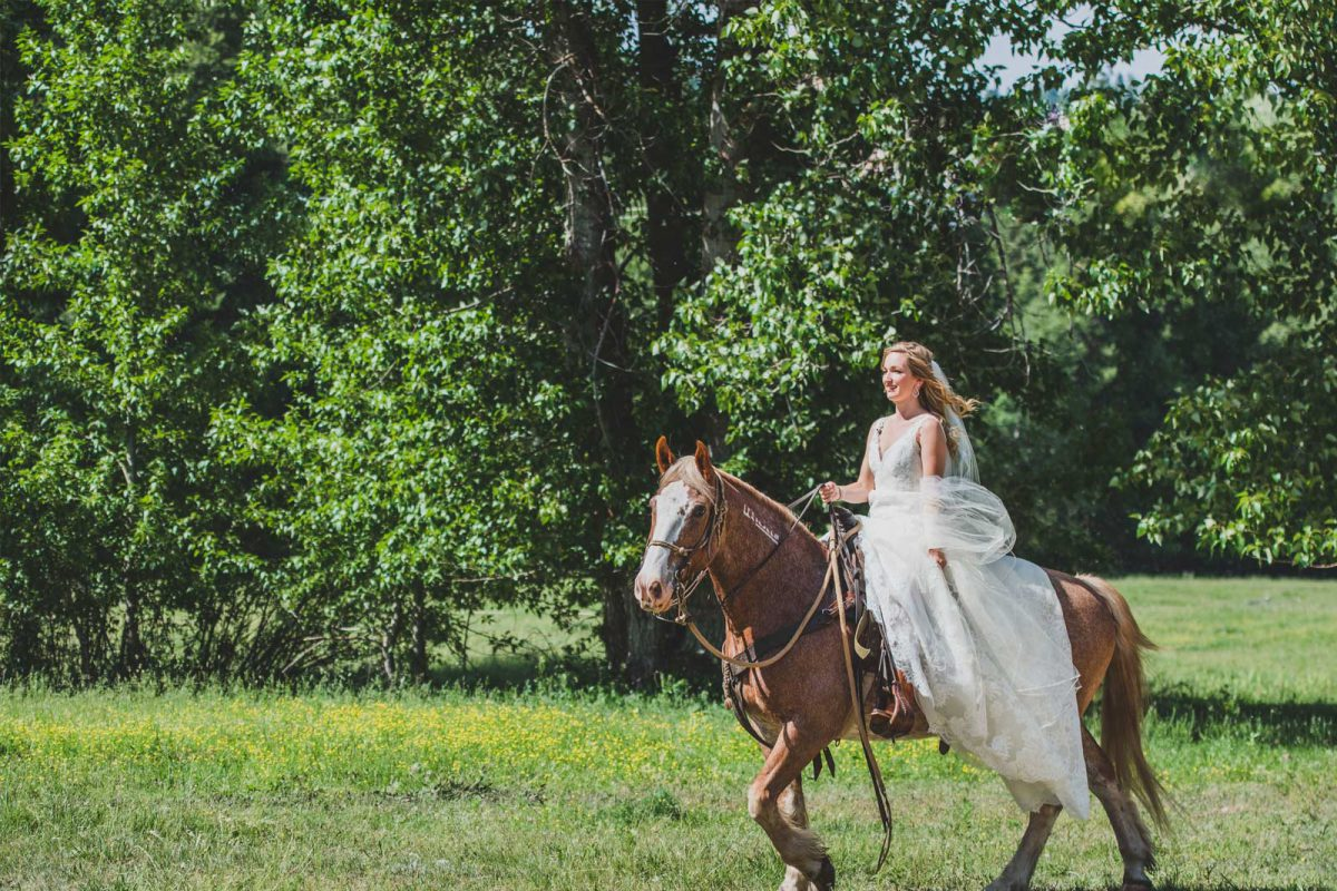 The bride riding into her wedding ceremony on horseback at Greenhorn Ranch