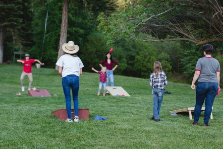 A family playing cornhole in the grass at Greenhorn Ranch