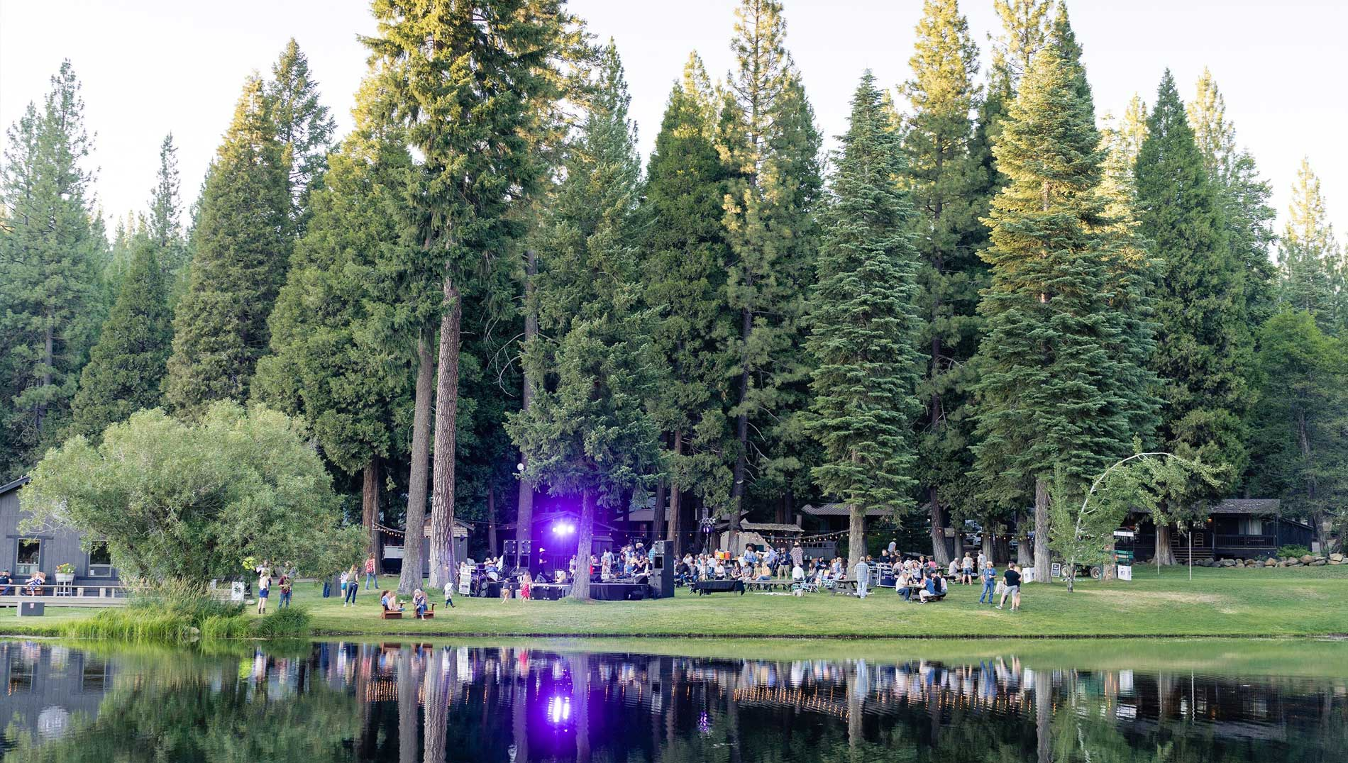 A large group of people dining at enjoying a concert by the lake at Greenhorn Ranch