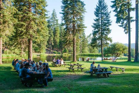 A large group of people dining at picnic tables by the lake at Greenhorn Ranch