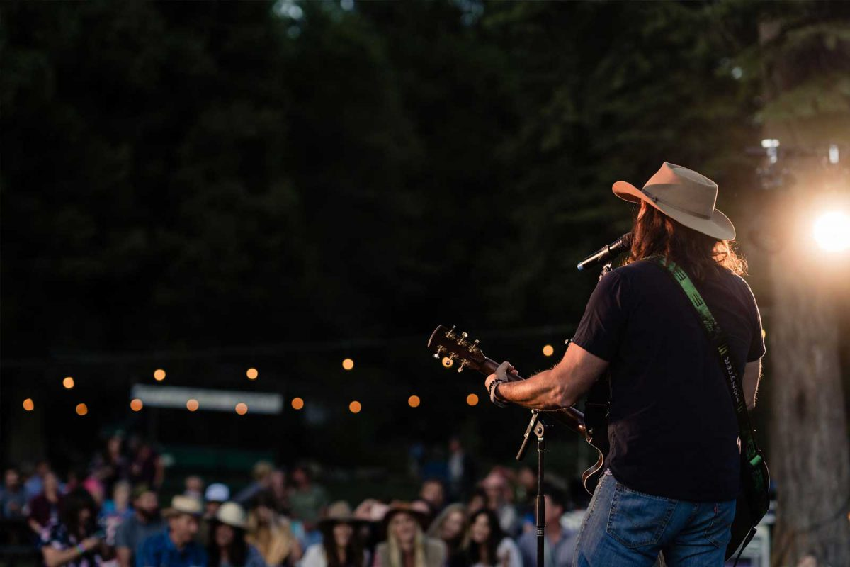 Looking over the musician's shoulder at the crowd at an outdoor concert at Greenhorn Ranch