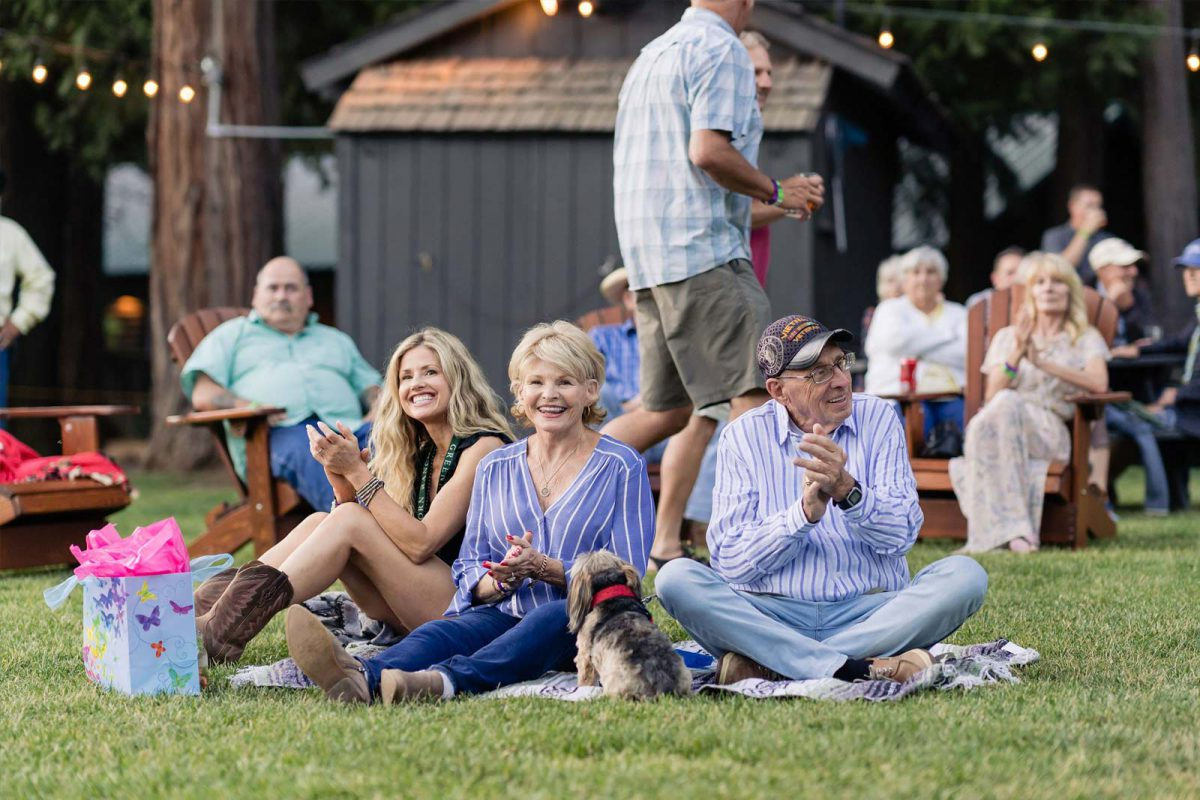 Guests at Greenhorn Ranch sitting on the grass for an outdoor concert.