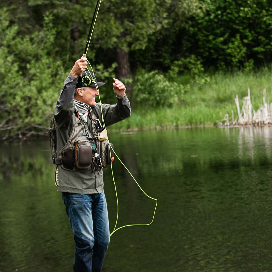 Fishing at Greenhorn Ranch - a fly fisherman in a vest and waders fly fishing at the lake at Greenhorn Ranch in Quincy, CA