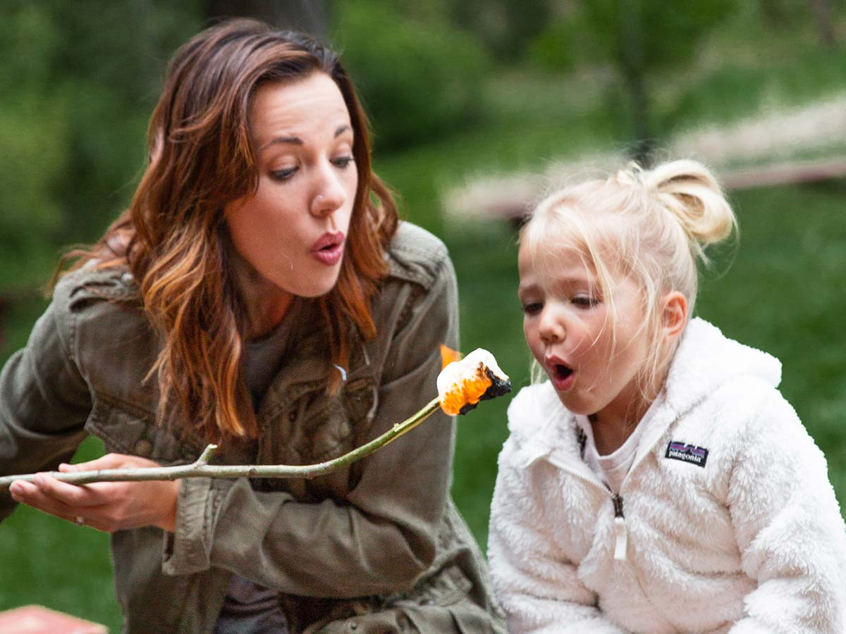 Mother and daughter roasting marshmallows over a campfire at Greenhorn Ranch in California