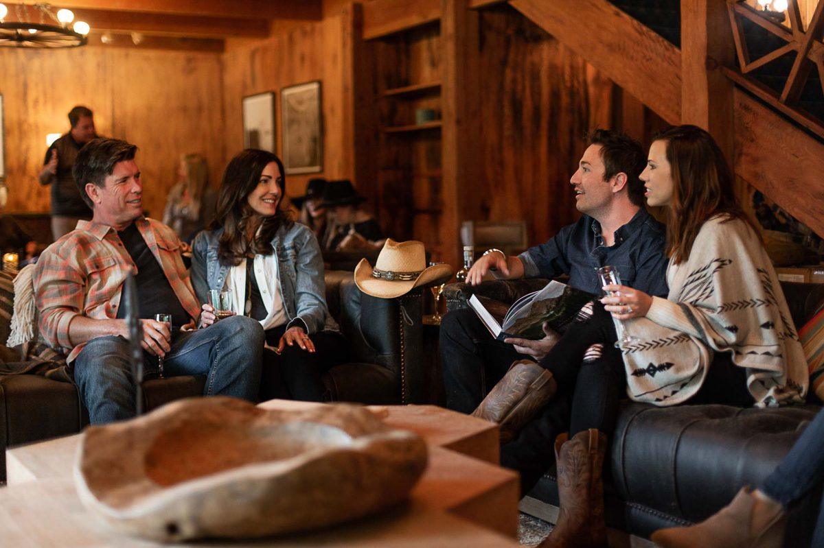 Four friends gathered around in the main lodge sharing the day's adventures