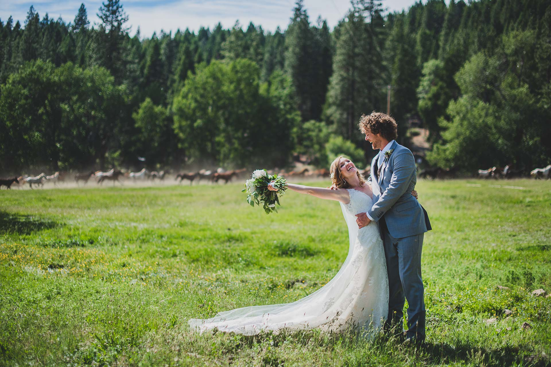 A bride & groom celebrating their wedding in a green grassy field at the Ranch