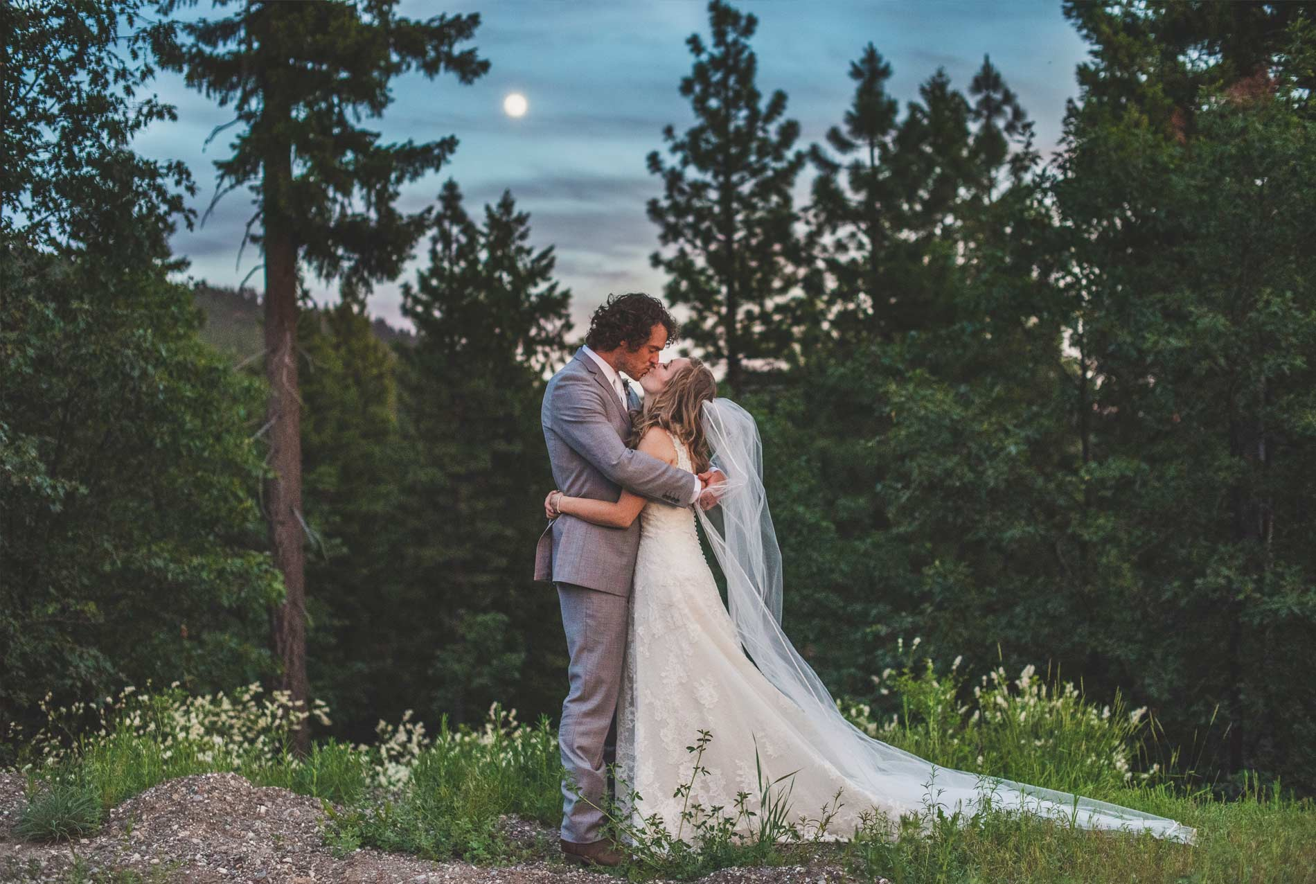 A bride & groom kissing under the dusk sky with trees around at Greenhorn Ranch