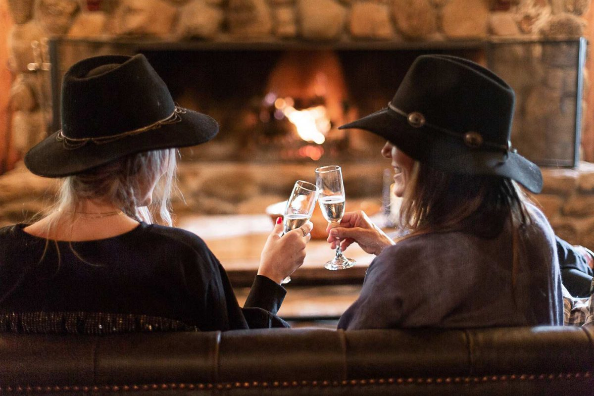 Two friends toasting champagne flutes in front of the fire in the Lodge at Greenhorn Ranch