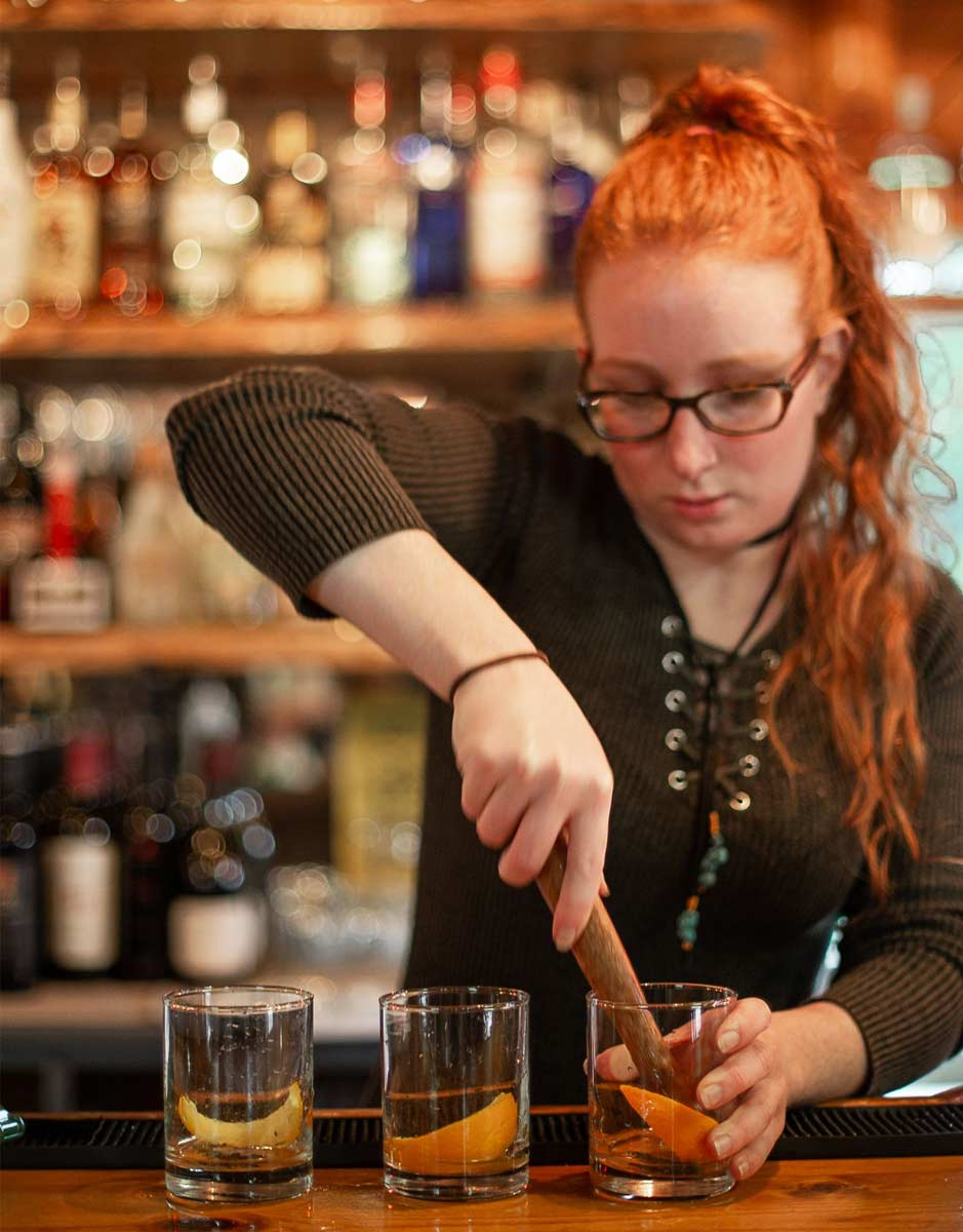 Bartender muddling herbs for a cocktail in the saloon
