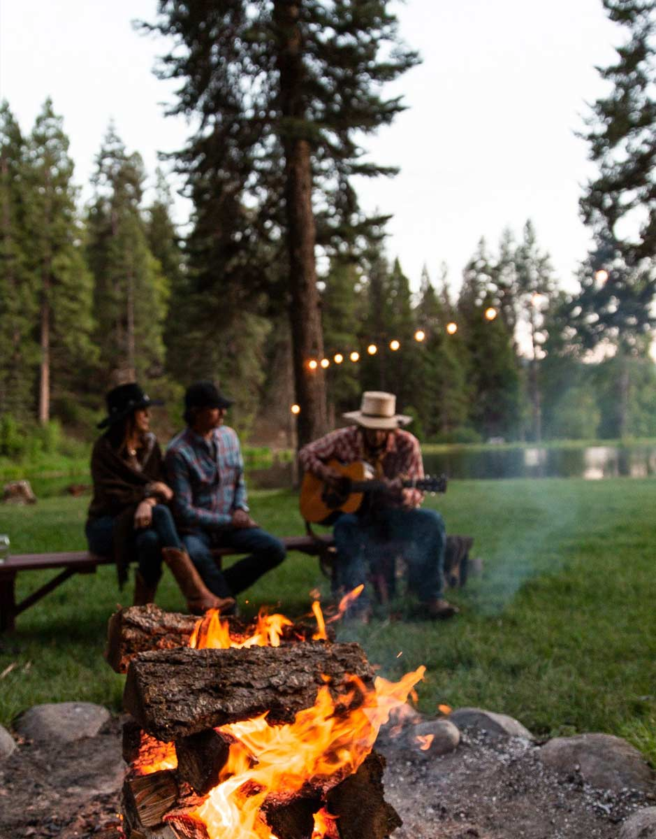Guests enjoying guitar music around the campfire