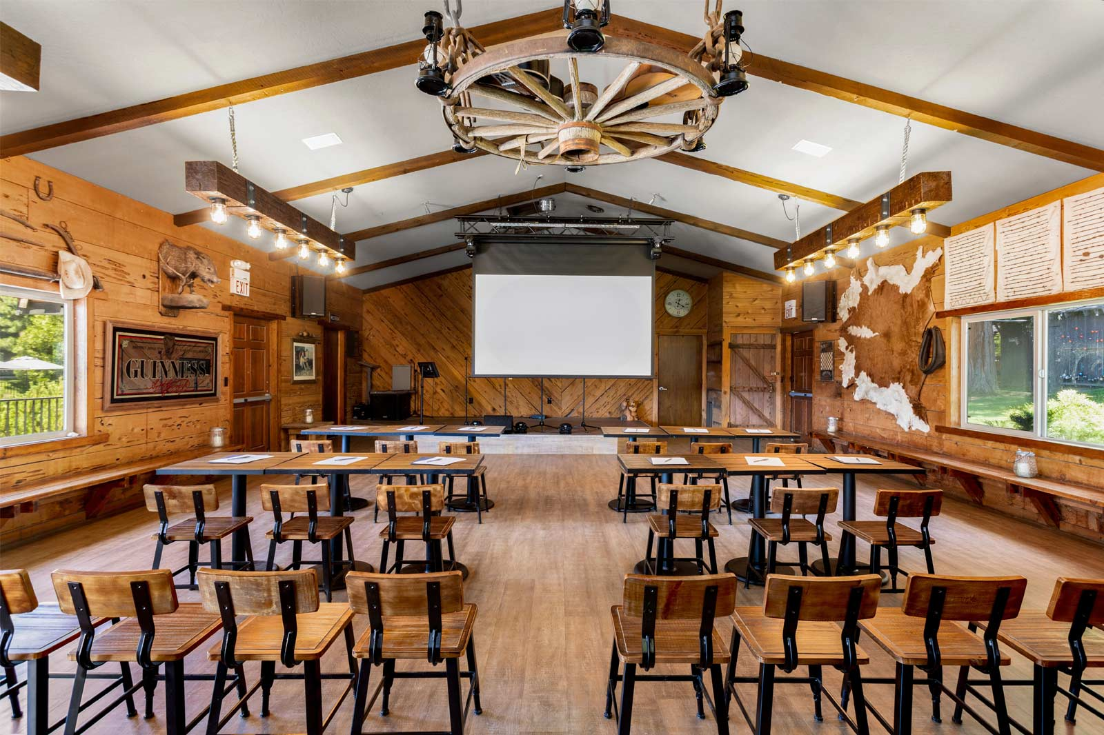 A meeting room inside a rustic ranch room with a presentation screen up front