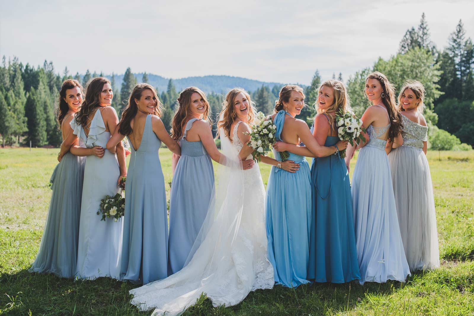 A bride and her bridesmaids arm in arm posing for a photo before her ranch wedding