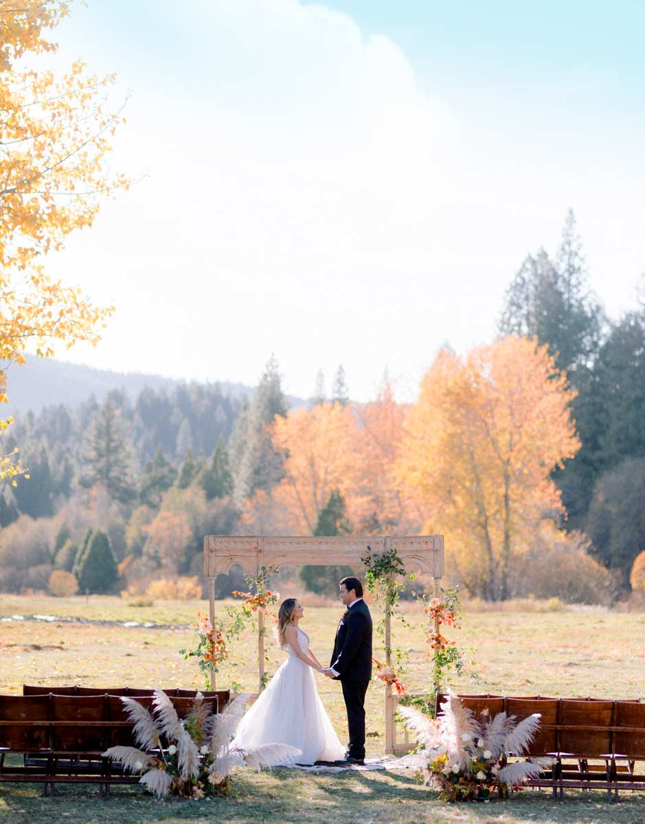 A bride and groom at an outdoor altar after their wedding