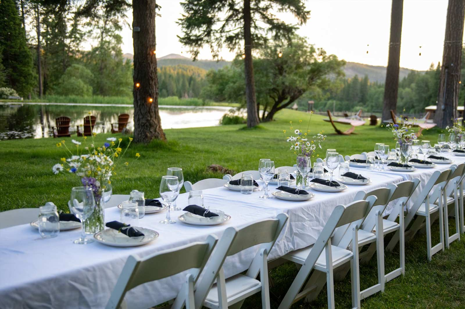 A table set with white linens outside by the Greenhorn pond