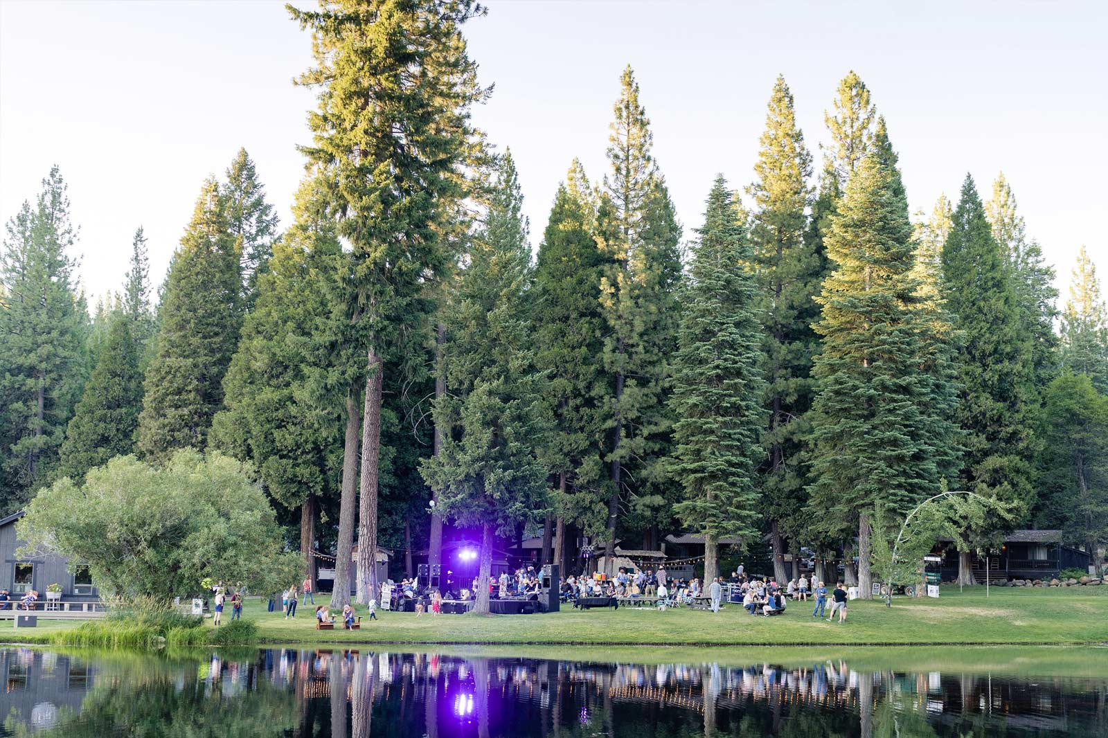 a look across the pond at a large group of Ranch guests at an outdoor concert