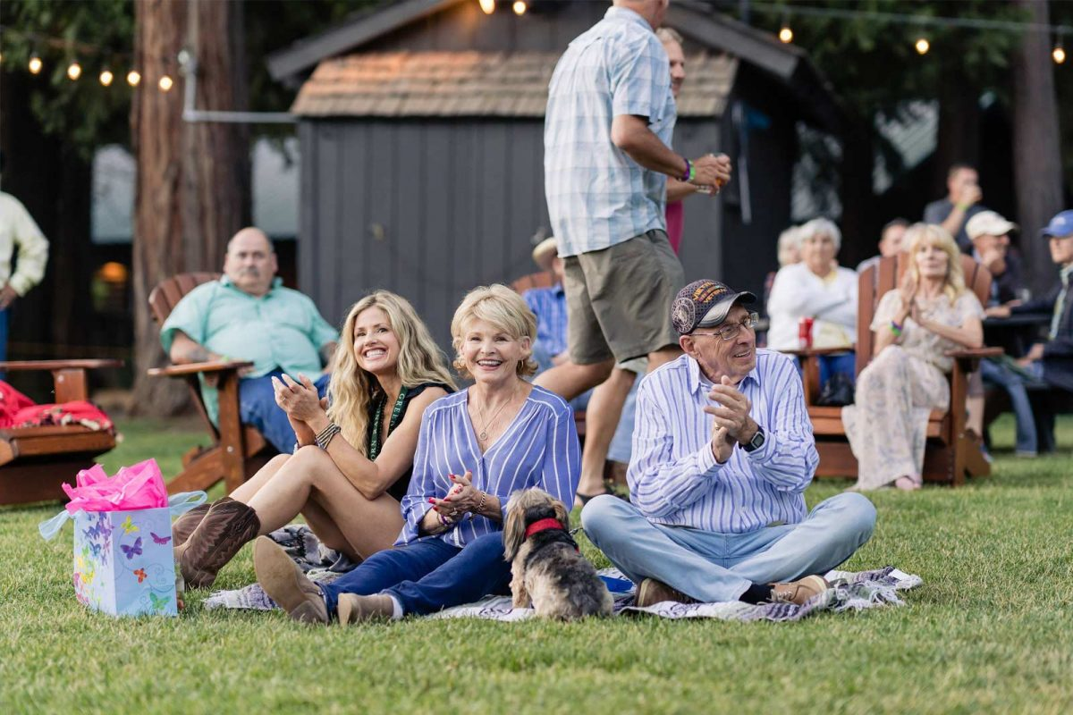 A small group of people sitting on green grass enjoying and clapping to music at an outdoor concert