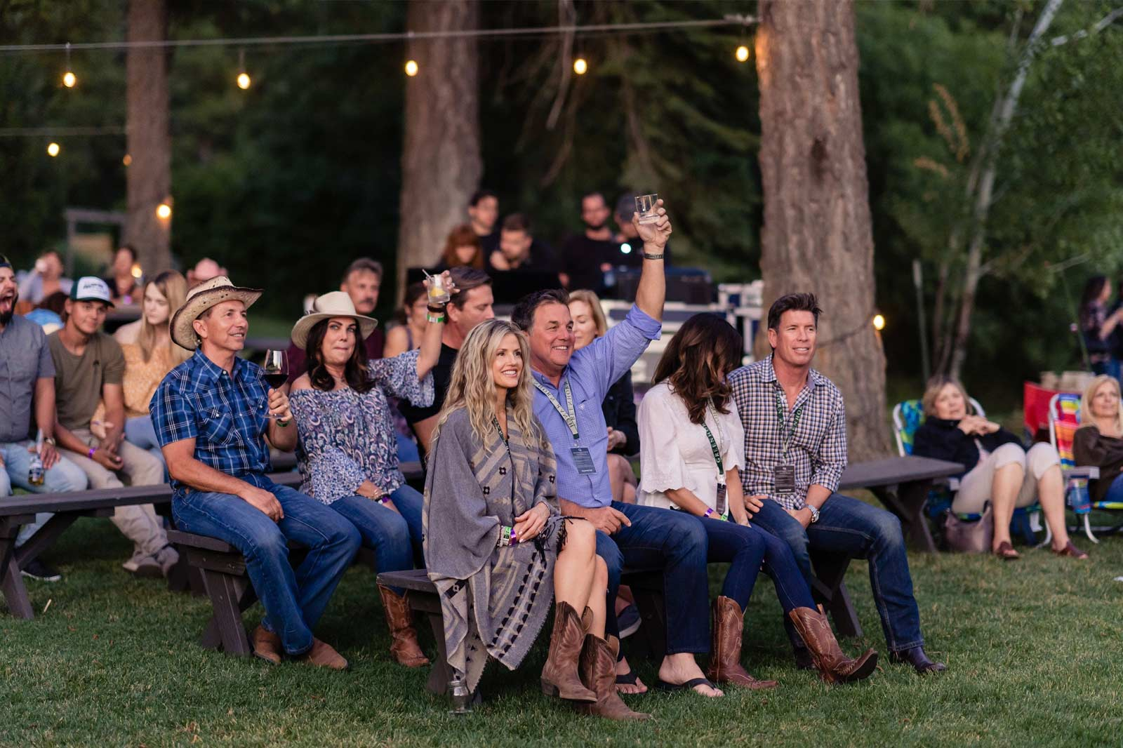 A group of people cheering at a concert at the Ranch