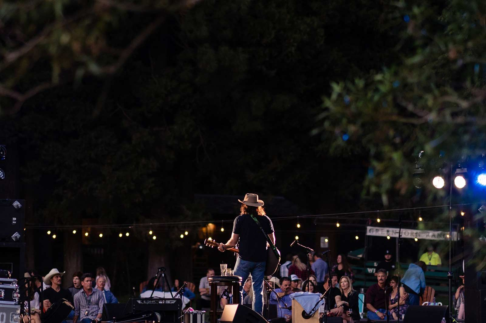 A solo guitarist on stage at an evening concert at Greenhorn Ranch
