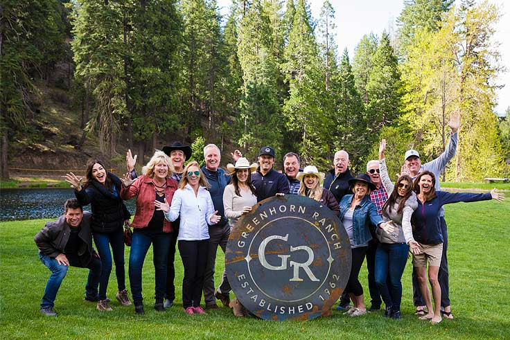 A group standing on green grassholding a big metal Greenhorn Ranch sign with pine trees behind them