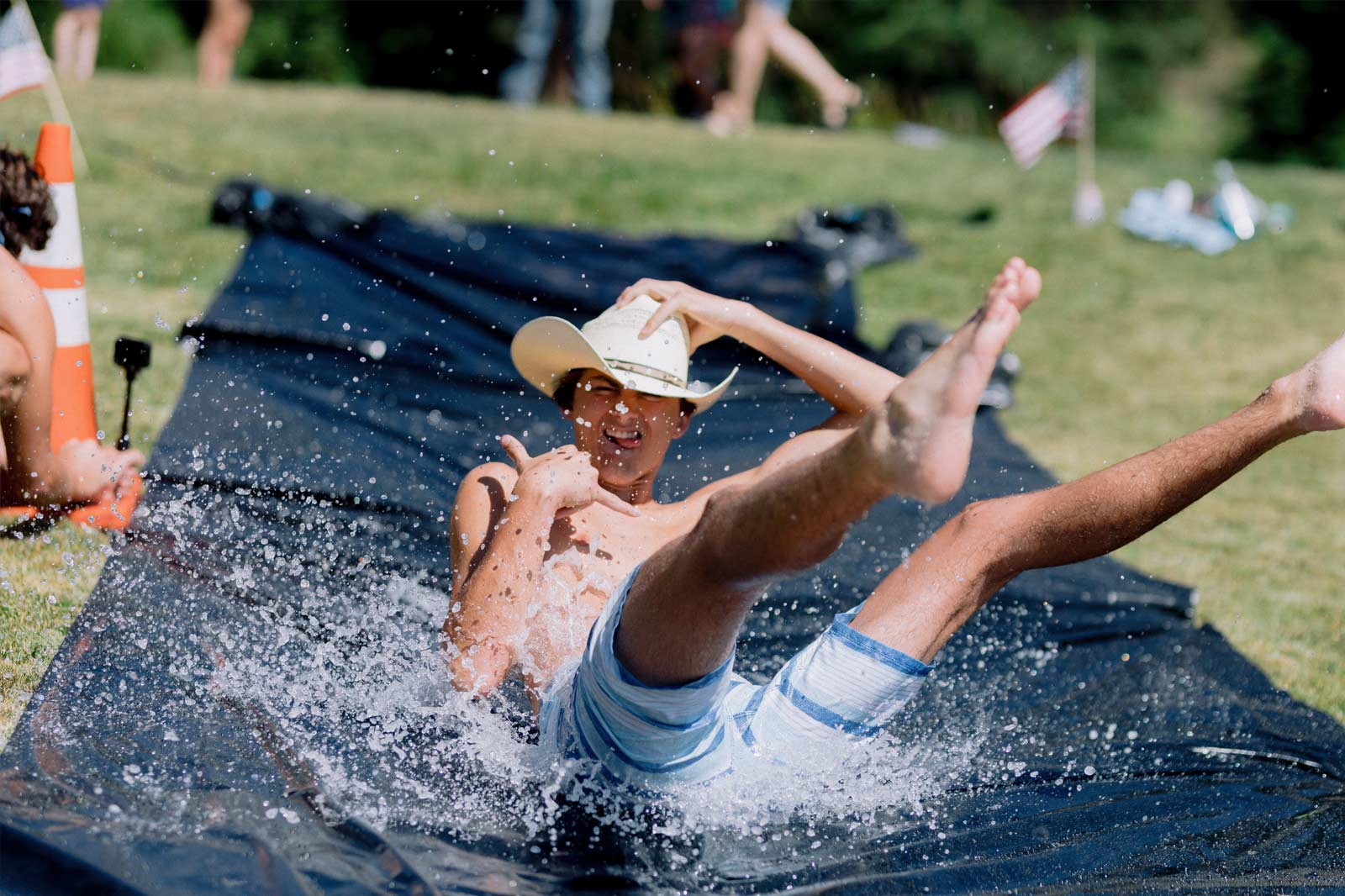 a young man wearing a cowboy hat and swim trunks enjoying a black plastic tarp water slide