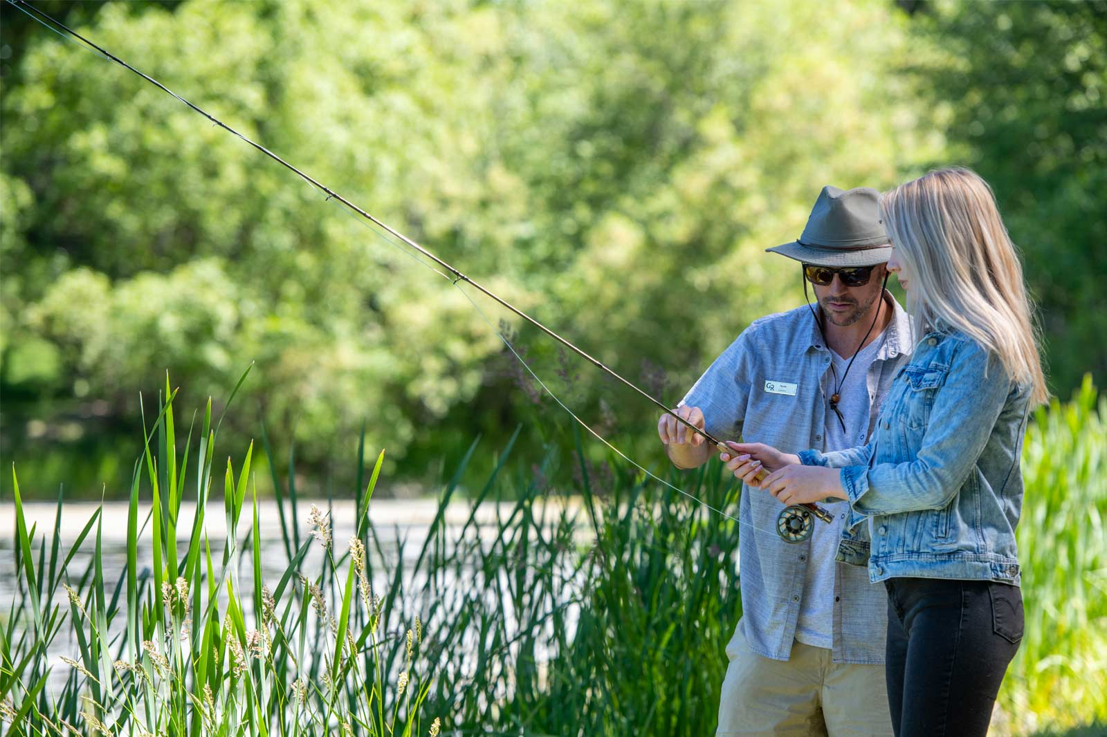 A fly fishing lesson at the pond, a blond woman receives instruction from a Greenhorn team member