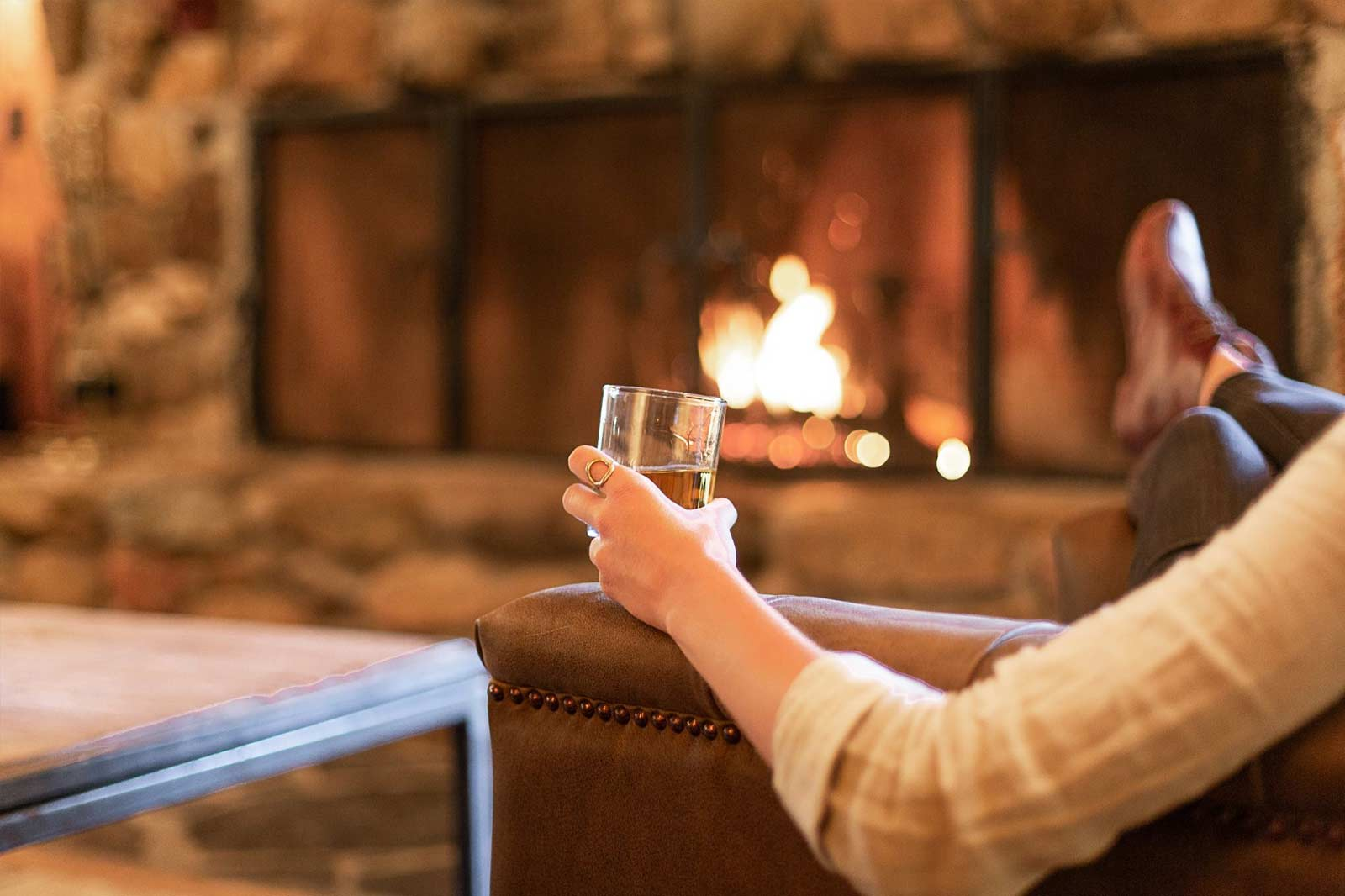 kick back and relax with a drink infront of a warm firepace