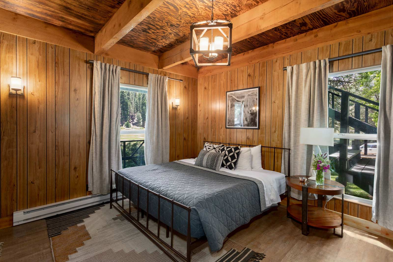 beautiful bedroom with wood floor to ceiling detail and a queen bed