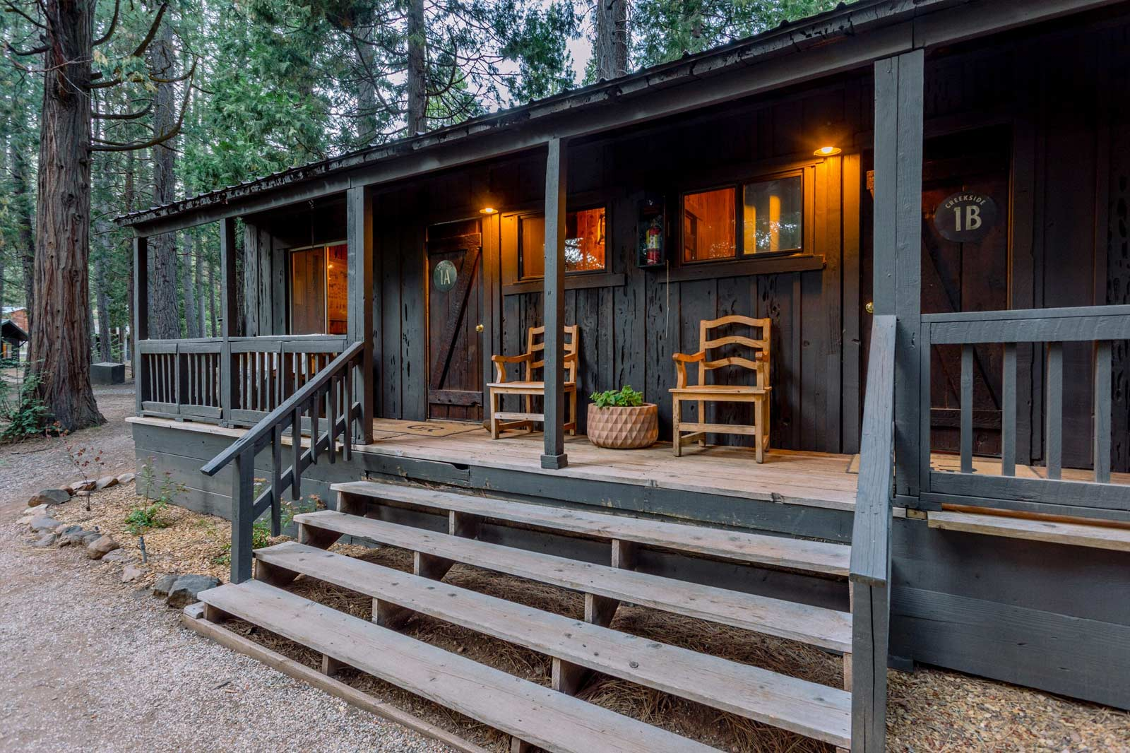 image of creekside cabin suite with stairs leading to two chairs and the entrance.